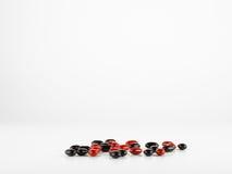 Красные и черные пилюльки витамина Стоковая Фотография