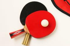 Красные и черные ракетки для игры настольного тенниса на белой предпосылке, взгляда сверху стоковая фотография