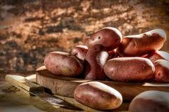 Красные картошки на деревянной доске Стоковые Фотографии RF