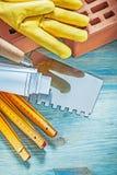 Красные кирпичи работая перчатки blueprints деревянный нож палитры метра Стоковые Фотографии RF