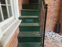 Красные кирпичи с зелеными лестницами и знаком который говорит штат только стоковое изображение