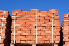 Красные кирпичи штабелированные в кубы Кирпичи склада Продукты кирпичных кладок хранения Стоковая Фотография RF