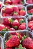 Красные клубники в пластичных коробках или корзины на рынке Стоковая Фотография