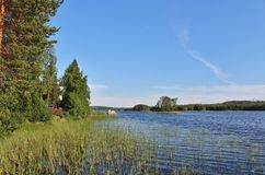 Красные коттеджи озером в Norrbotten стоковое фото rf
