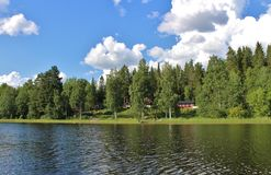 Красные коттеджи озером в Norrbotten стоковые изображения rf