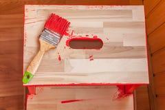Красные краска и щетка на деревянном стуле стоковое изображение rf