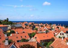 Красные крыши и океан на городке Gudhjem в Дании Стоковые Изображения