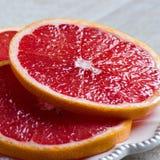 Красные куски грейпфрута на плите Стоковые Изображения