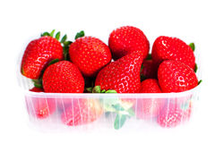 Красные клубники ягоды в пластичной коробке изолированной на белом backg Стоковое Изображение