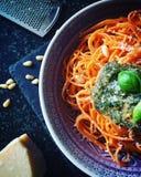Красные макаронные изделия спагетти с зелеными свежими соусом песто, листьями базилика, гайками сосны и сыром Стоковые Фотографии RF