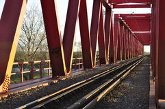 Красные мост и железная дорога на заходе солнца стоковые изображения rf