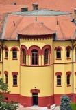 Красные окна на желтом здании в небольшом европейском городе стоковая фотография rf