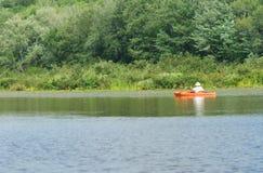 Красные оранжевые каяк или каное на спокойном озере Стоковые Изображения