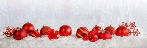 Красные орнаменты рождества гребут на предпосылке bokeh рождества снежной стоковое фото