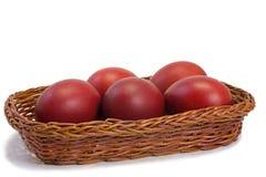 Красные пасхальные яйца в корзине на белой предпосылке. Стоковое фото RF