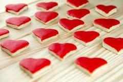 Красные печенья рождества в сердце формируют лежать на древесине Стоковое Фото