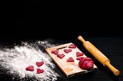 Красные печенья сердца на черной таблице, печь на день валентинки Стоковые Изображения