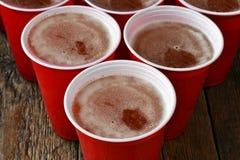 Красные пластичные выпивая чашки заполненные с пивом Стоковое Изображение RF
