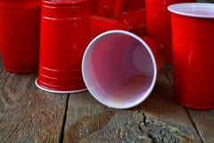 Красные пластичные выпивая чашки и разлитое пиво Стоковые Фотографии RF