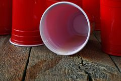 Красные пластичные выпивая чашки и разлитое пиво Стоковые Изображения
