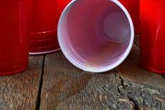 Красные пластичные выпивая чашки и разлитое пиво Стоковые Изображения RF