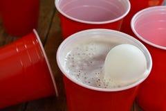 Красные пластичные выпивая чашки и разлитое пиво Стоковая Фотография RF