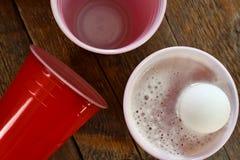 Красные пластичные выпивая чашки и разлитое пиво Стоковые Фото