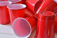 Красные пластичные выпивая чашки Стоковые Фото