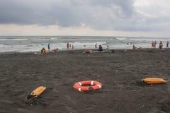 Красные пластичные приборы и sunbeds спасения флотирования на пляже пасмурная погода, overcast Стоковое Фото