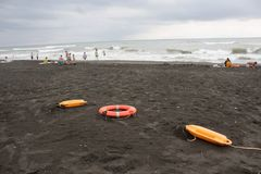 Красные пластичные приборы и sunbeds спасения флотирования на пляже погода тускловата Стоковые Изображения