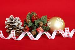 Красные подарки на ели увенчивают, яблоко сосны с снегом на ем и золотой шарик для украшения партий на красной предпосылке стоковые фотографии rf