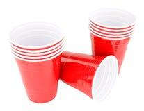Красные пластичные устранимые выпивая чашки Стоковые Фото