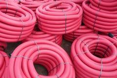 Красные рифлёные пластичные трубы используемые для подземных электрических линий Стоковая Фотография RF