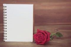 Красные розы и белая книга на деревянной предпосылке, космосе экземпляра для текста стоковое фото