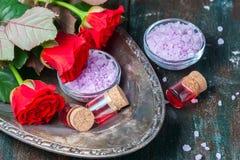 Красные розы и бутылки эфирного масла на темной деревенской предпосылке, селективном фокусе Стоковые Фотографии RF