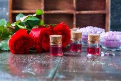 Красные розы и бутылки эфирного масла на темной деревенской предпосылке, селективном фокусе Стоковое фото RF