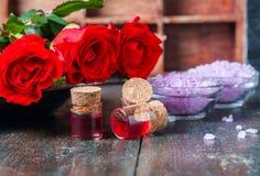 Красные розы и бутылки эфирного масла на темной деревенской предпосылке, селективном фокусе Стоковые Изображения