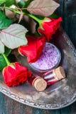 Красные розы и бутылки эфирного масла на темной деревенской предпосылке, селективном фокусе Стоковые Изображения RF