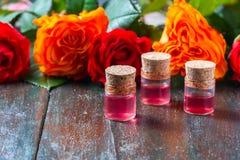 Красные розы и бутылки эфирного масла на темной деревенской предпосылке, селективном фокусе Стоковые Фото