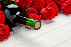 Красные розы и вино на белой предпосылке Стоковые Изображения