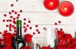 Красные розы и вино на белой предпосылке Стоковая Фотография