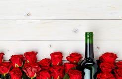Красные розы и вино на белой предпосылке Стоковое Фото