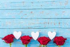 Красные розы и граница сердец на свете - голубой деревянной предпосылке для день ` s Wedding или валентинки Стоковые Изображения RF