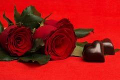 Красные розы и конфеты в форме сердца на красном цвете Стоковое Изображение