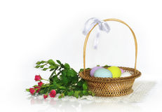 Красные розы и корзина с пасхальными яйцами Стоковые Изображения