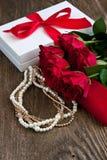 Красные розы и подарочная коробка на деревянной предпосылке Стоковые Изображения RF