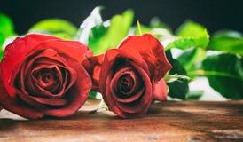 Красные розы на деревянном столе стоковое фото