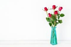 Красные розы цветут букет в зеленой вазе на белой предпосылке Стоковая Фотография