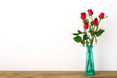 Красные розы цветут букет в зеленой вазе на белой предпосылке Стоковая Фотография RF