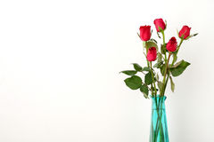 Красные розы цветут букет в зеленой вазе на белой предпосылке Стоковые Фотографии RF